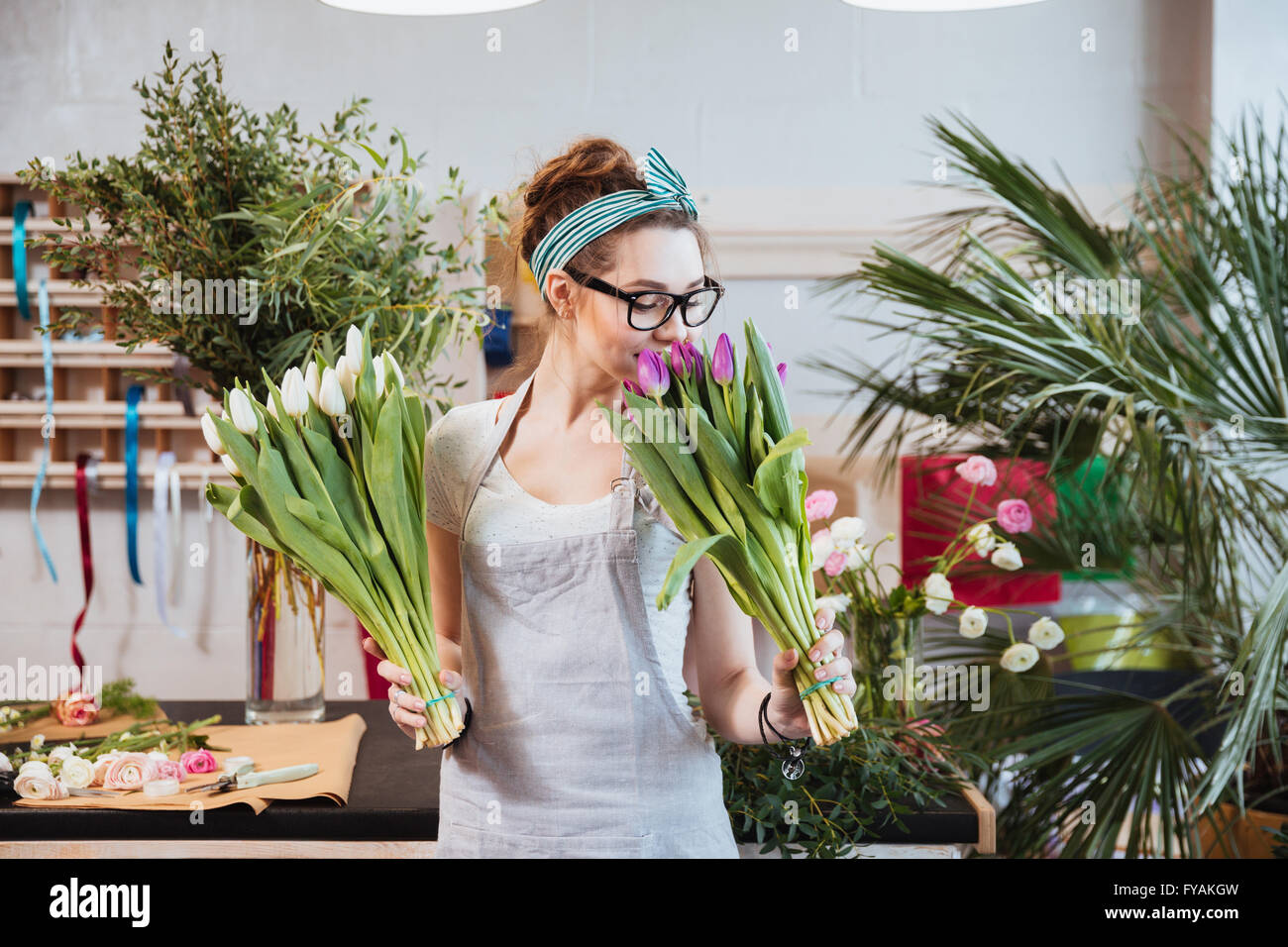 Happy lovely young woman florist holding and smelling tulips in flower shop Stock Photo