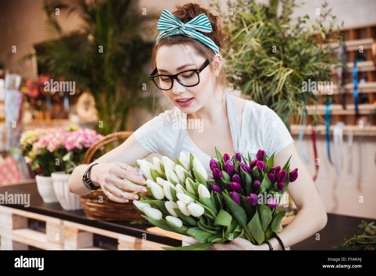 Cute lovely young woman florist in glasses taking care of tulips in flower shop - Stock Image