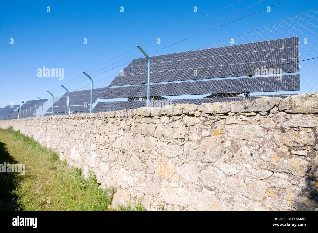 Solar panels behind wire fence. Solar energy production plant. Toledo province. Castile La Mancha. Spain. - Stock Image