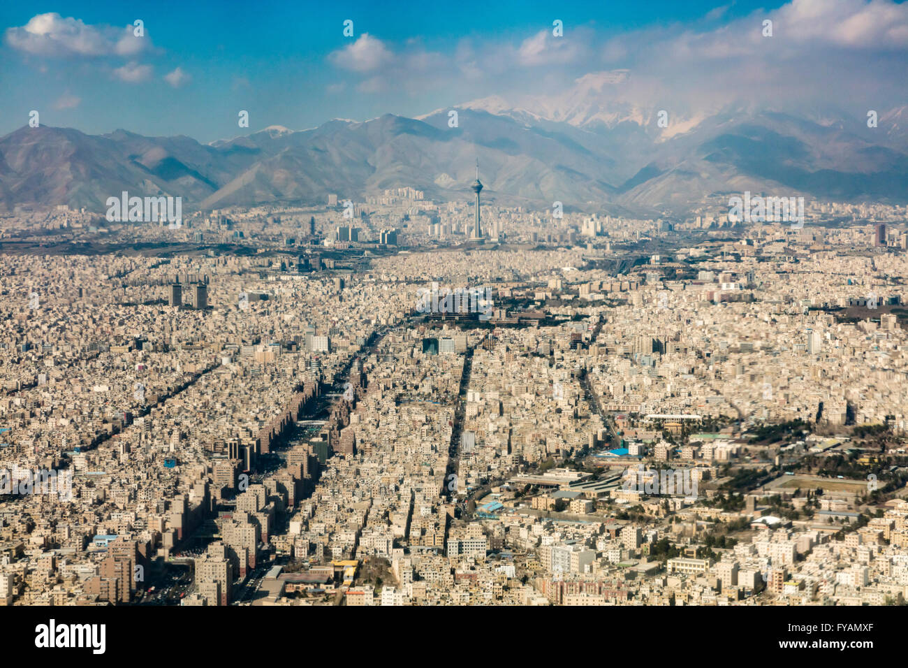 Aerial view of concrete sprawl of Tehran Iran with the snowcapped Alborz Mountains in background - Stock Image