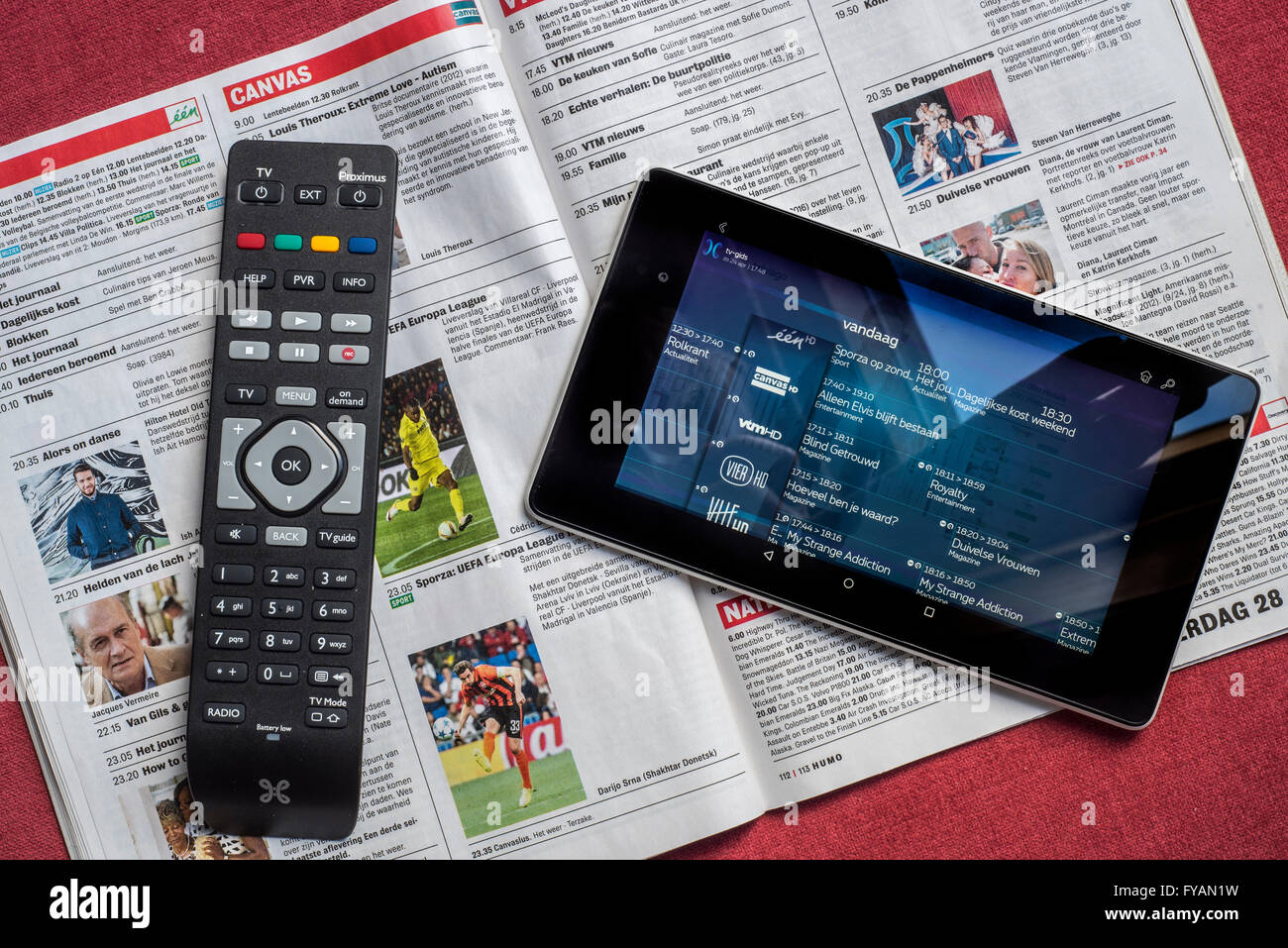 Remote control and tablet showing television channels on top of open Belgian magazine showing the tv programmes' - Stock Image