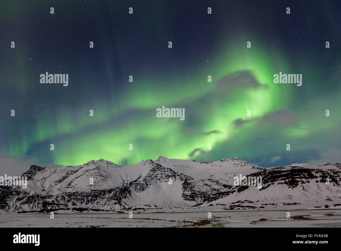 Northern Lights / Aurora borealis, weather phenomenon showing light display over the snow covered mountains in winter, - Stock Image