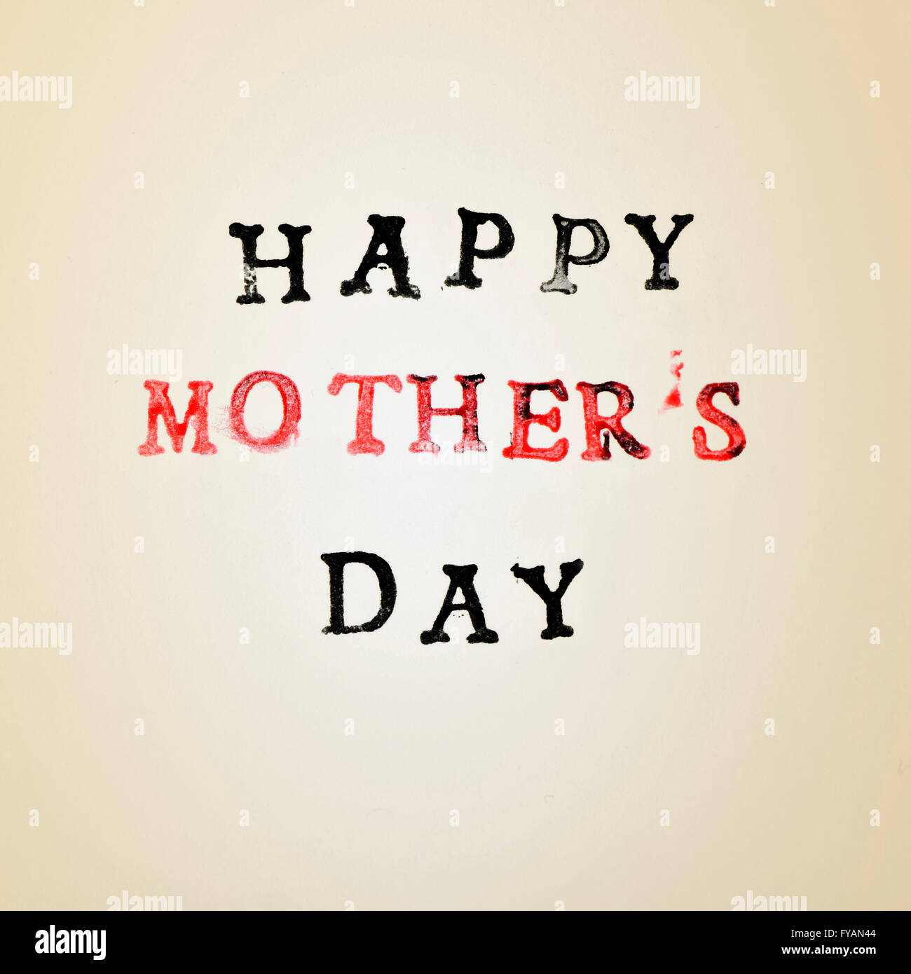 the text happy mothers day printed in black and red in a beige gradient background - Stock Image