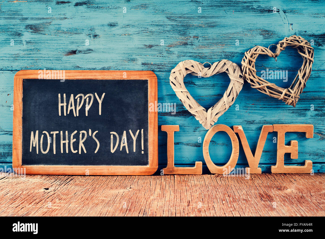 the text happy mothers day written in a chalkboard placed next to some wooden letters forming the word love and - Stock Image