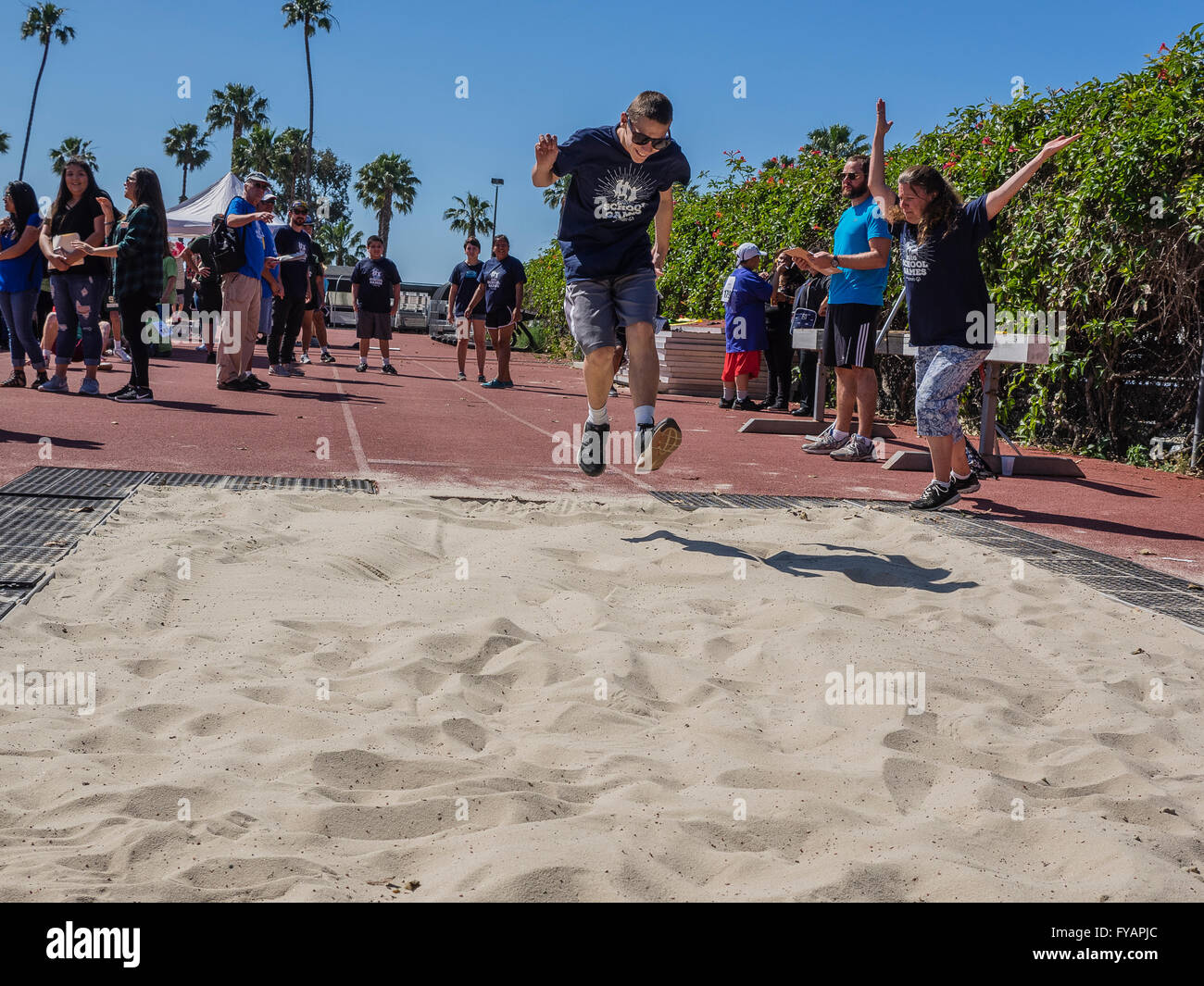 A disabled teenage boy jumps in the broad jump at the Southern California Special Olympics held at La Playa Stadium. - Stock Image