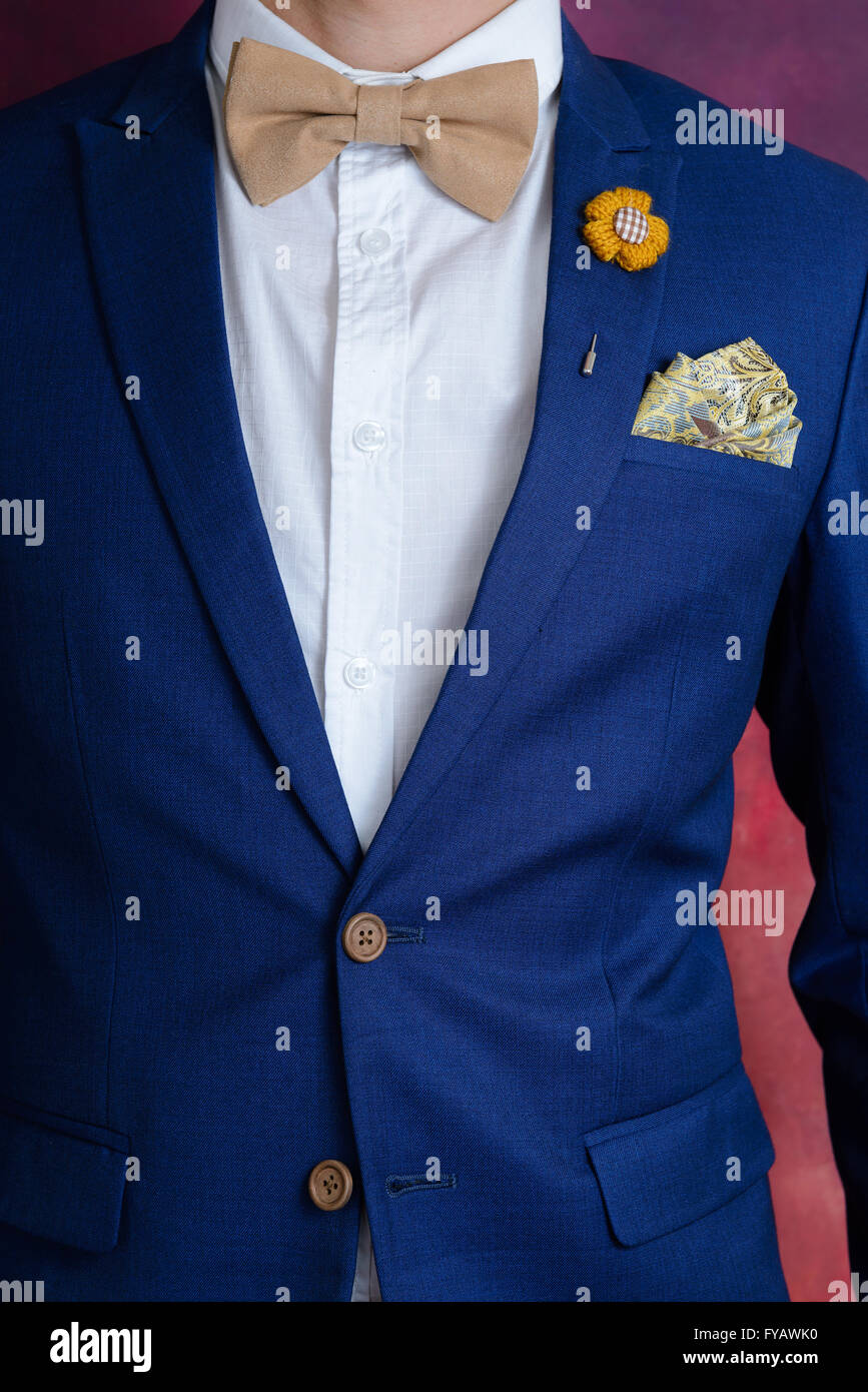 man in blue suit with brown bow tie flower brooch and classic