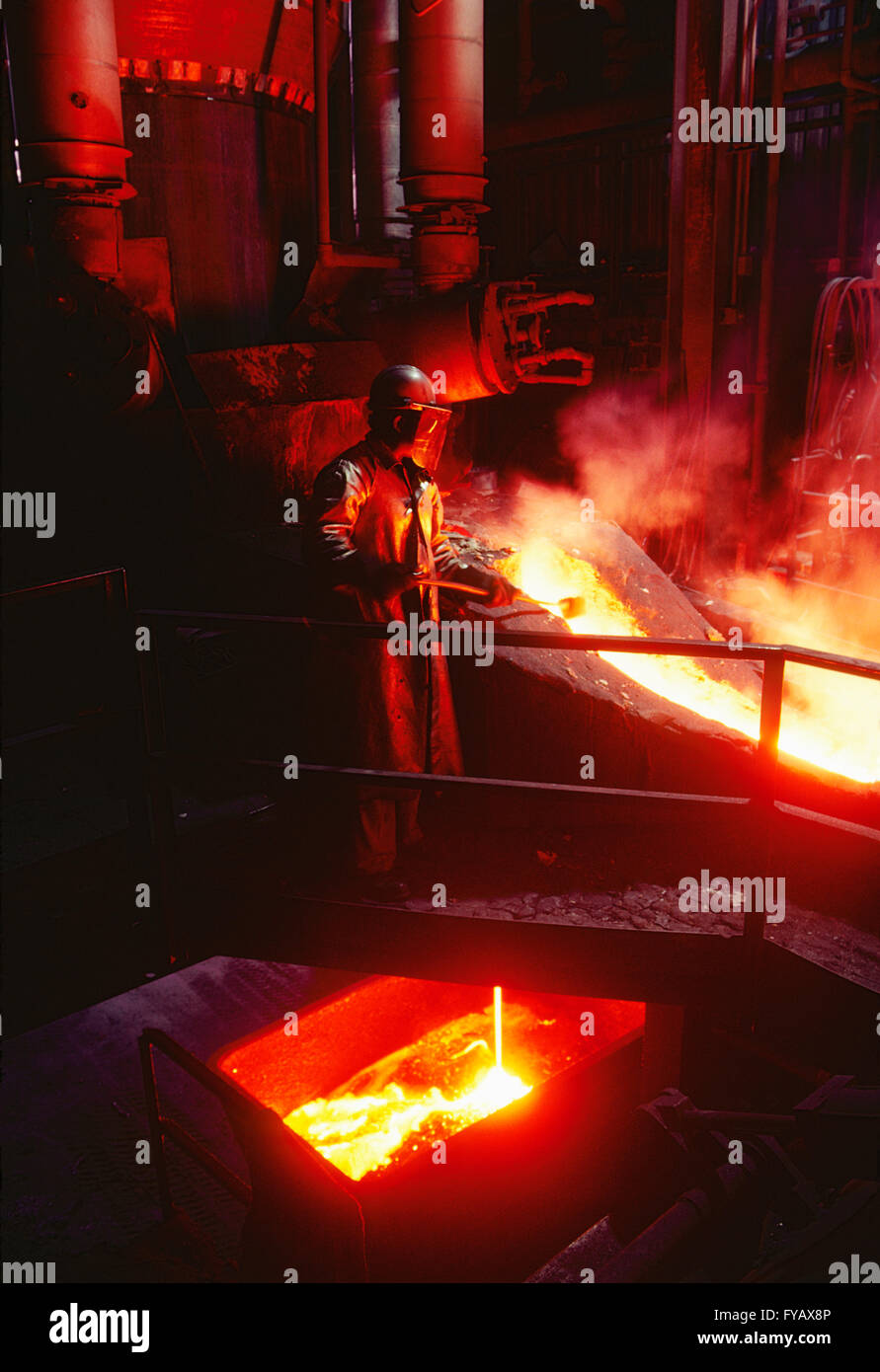 Worker monitors hot molten steel pour in foundry - Stock Image