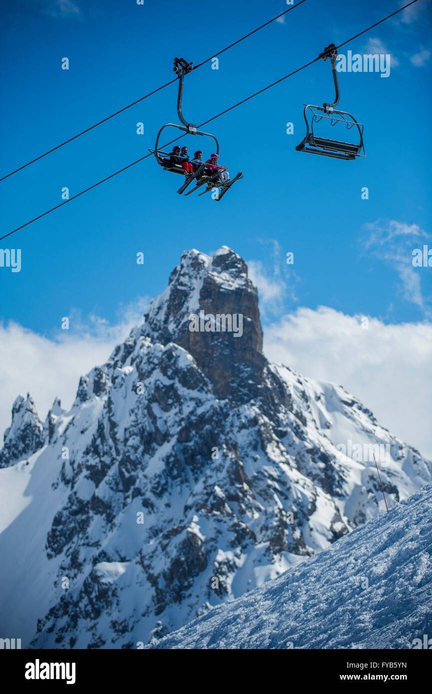 A group of skiers on a chairlift in front of L'aiguille du Fruit in the ski resort of Courchevel in the French - Stock Image