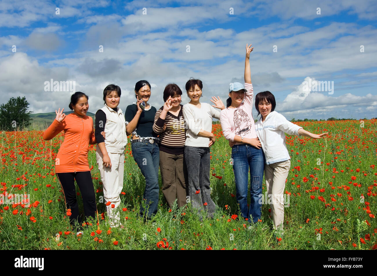 Group of young people in a field of red poppies, Kyrgystan - Stock Image