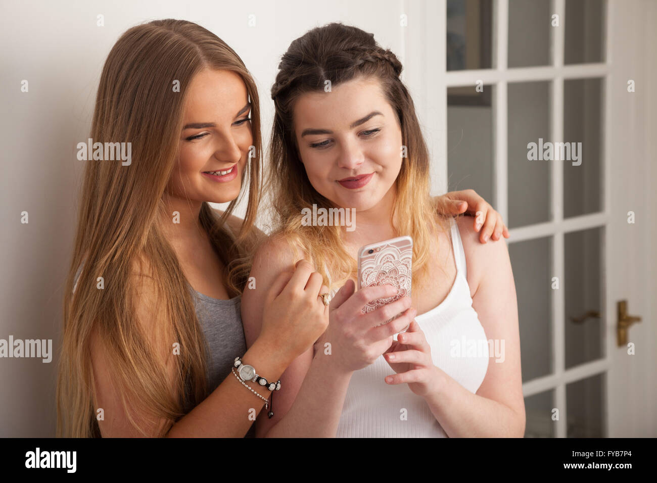 Two teenage girls looking at a mobile phone together. - Stock Image