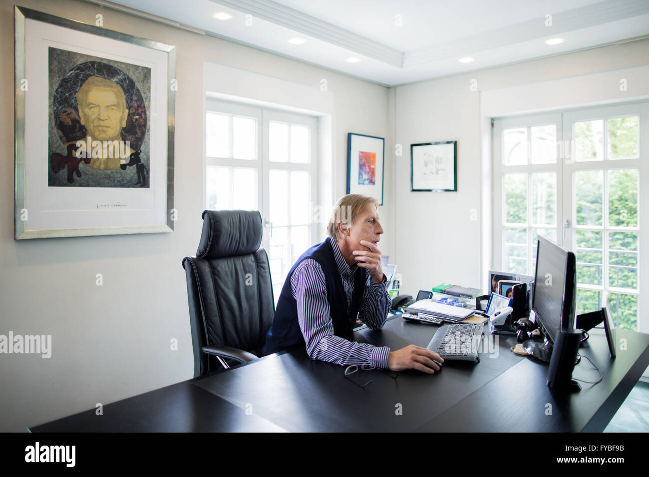 dpa-Exclusive - Soccer coach Christoph Daum works on his computer as he sits in front of a replicated portrait painting - Stock Image