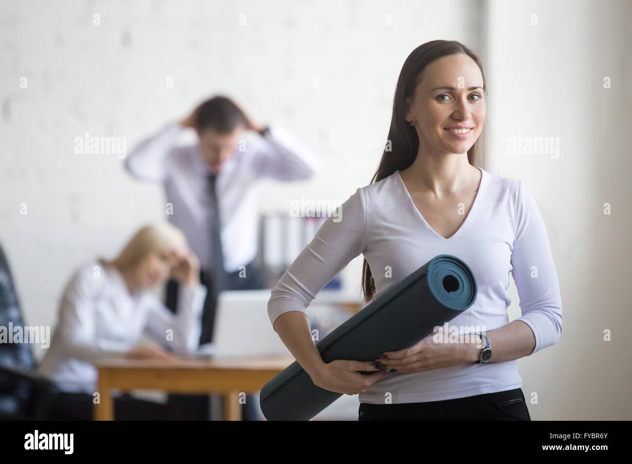 Business and healthy lifestyle concept. Portrait of beautiful sporty calm young office woman standing with yoga - Stock Image