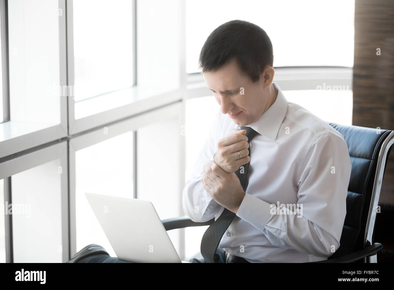 Handsome young stressed businessman sitting in his office using laptop. Caucasian businessperson touching his aching - Stock Image