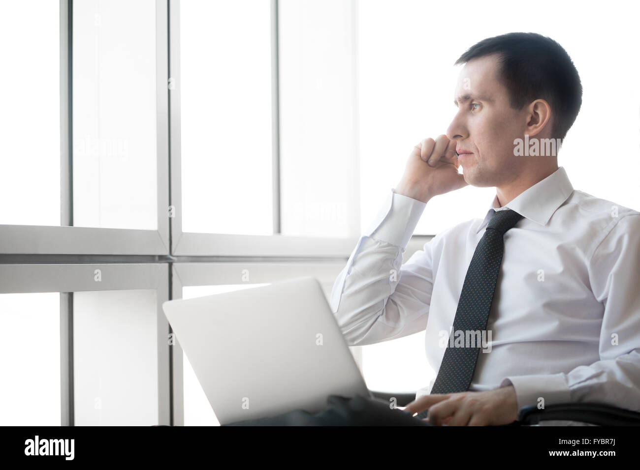 Portrait of serious handsome young business man working on laptop computer and making call. Caucasian businessperson - Stock Image