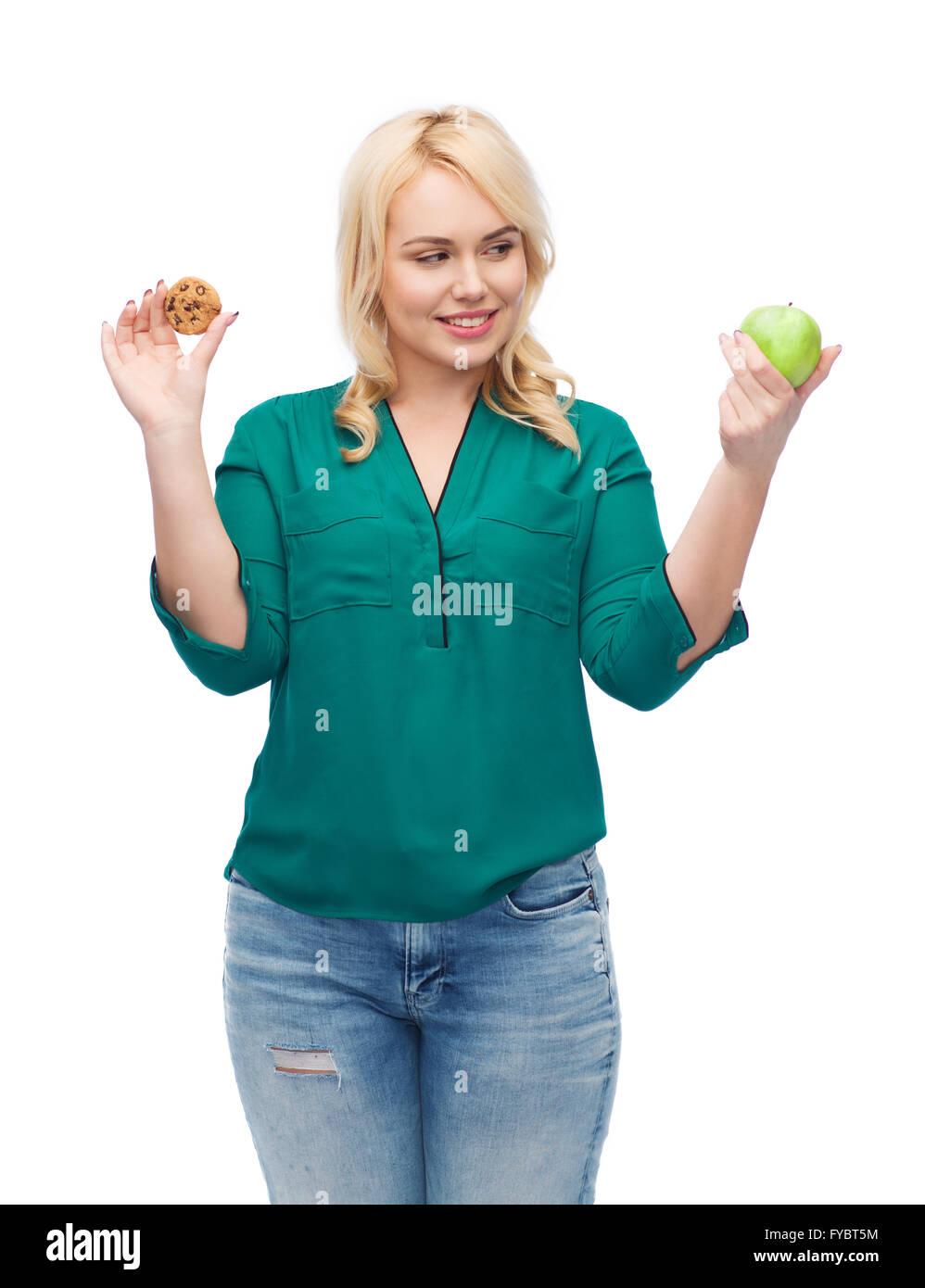 smiling woman choosing between apple and cookie - Stock Image