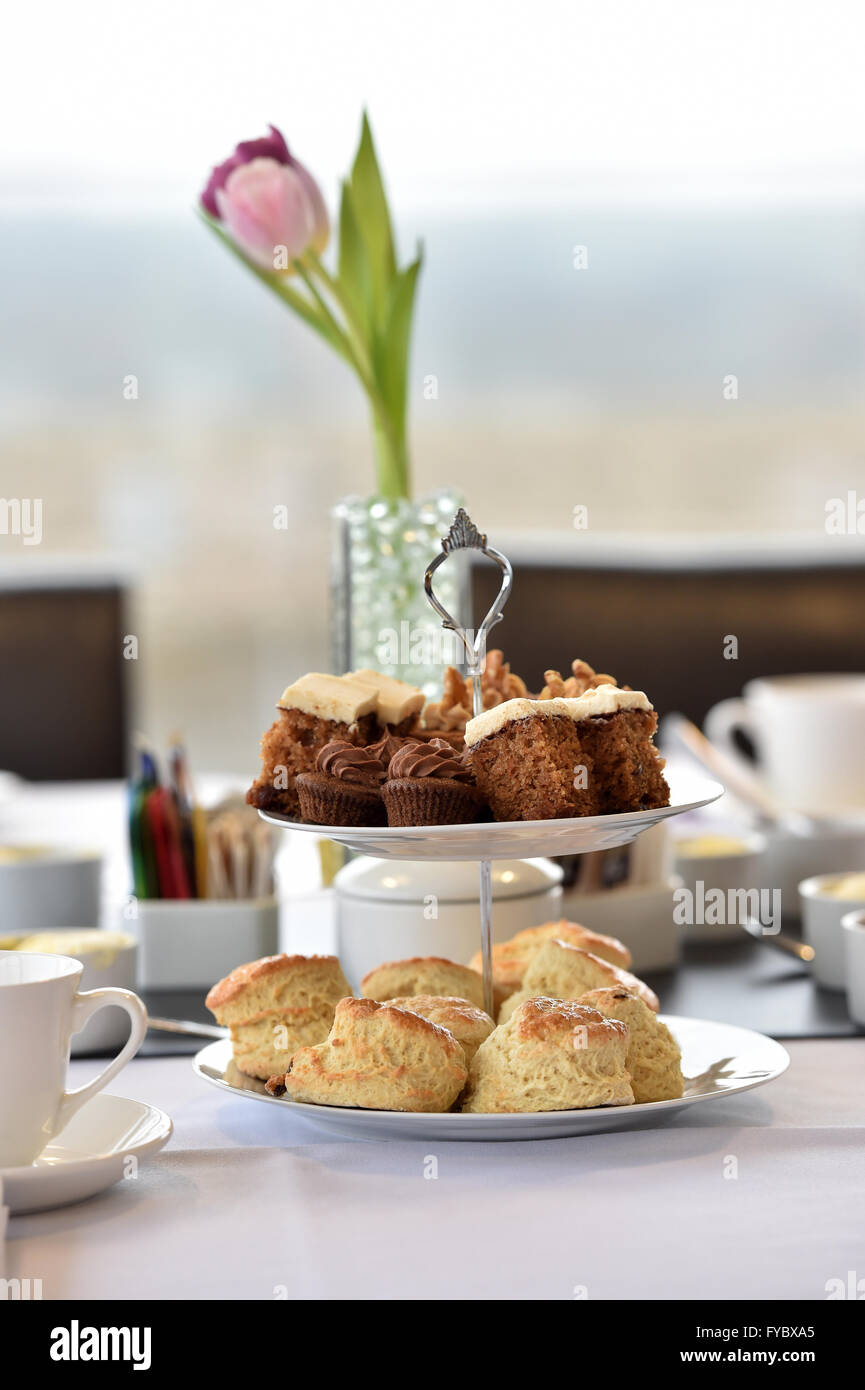 Afternoon tea in office environment Cake Scones  2 tier cake stand  Tulip flowers - Stock Image