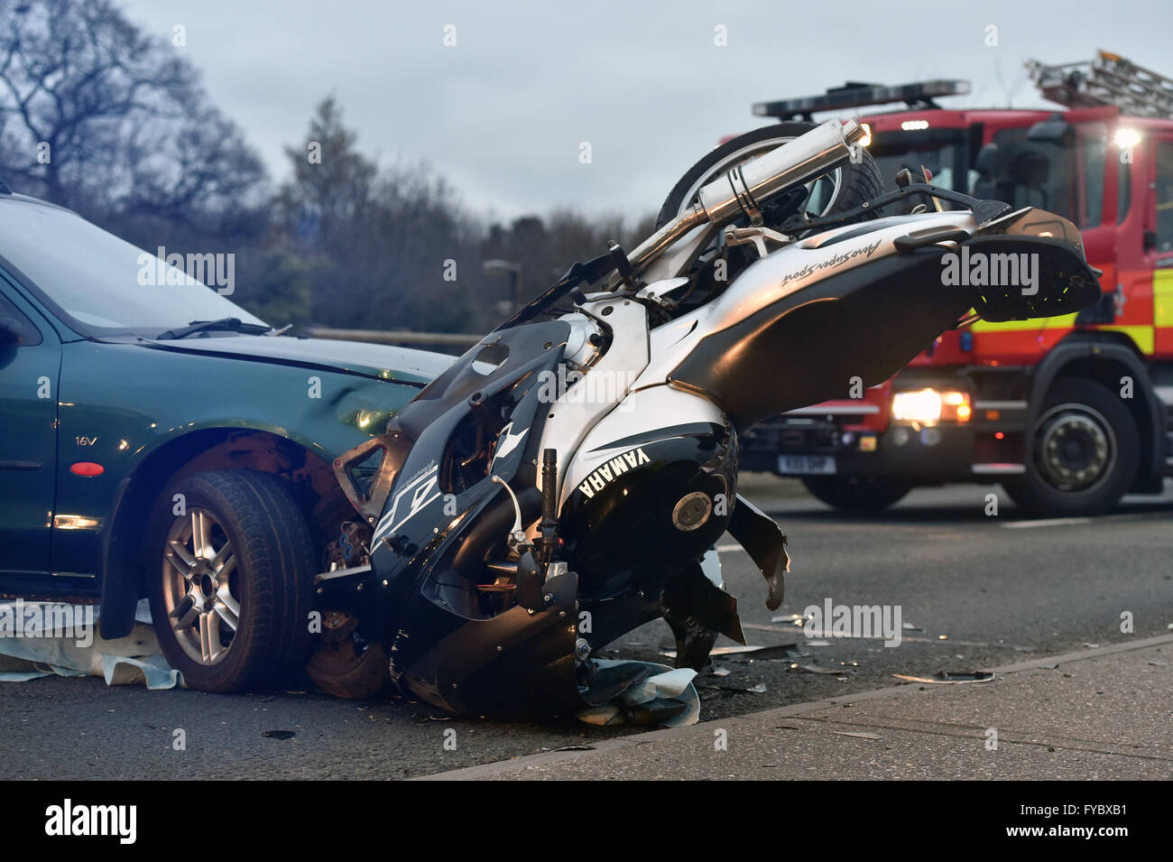 Motorbike crash into front of car. Yamaha Aero Super Sport bike upside down Fire engine in back ground   scene late - Stock Image