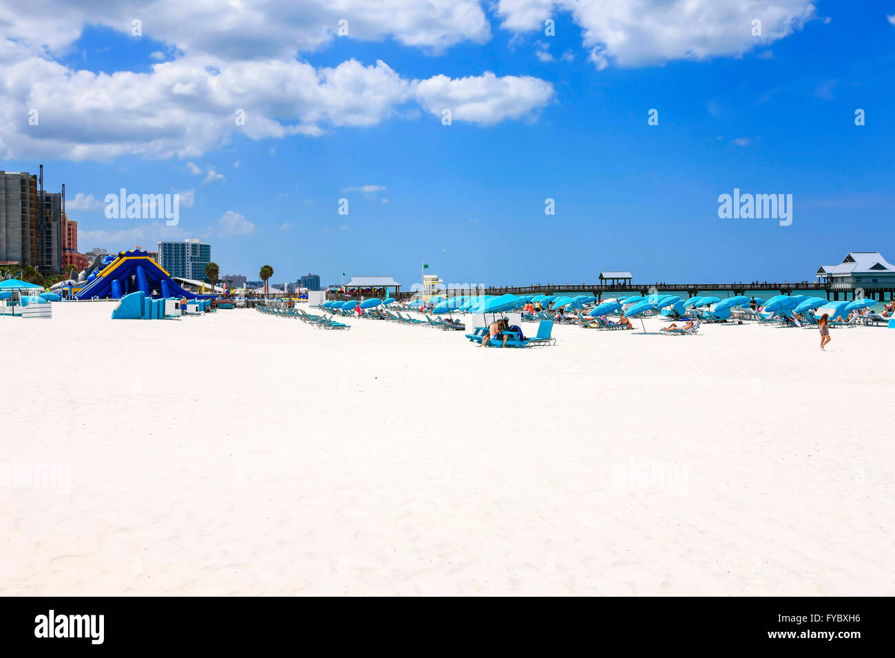 Blue umbrellas, cabanas and people on Clearwater beach Florida, voted the number one beach in America - Stock Image