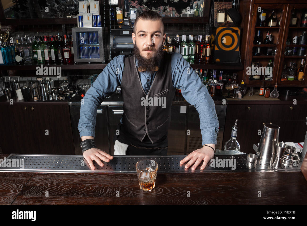 Confident Barman serving cocktail at the bar. - Stock Image