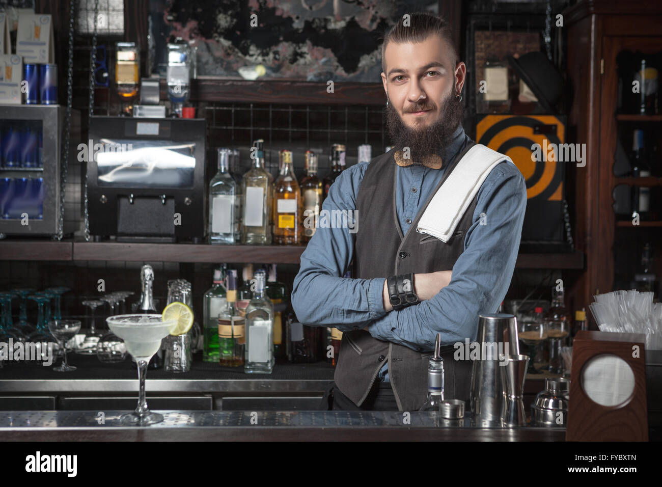 Happy barman at work with crossed hands. - Stock Image