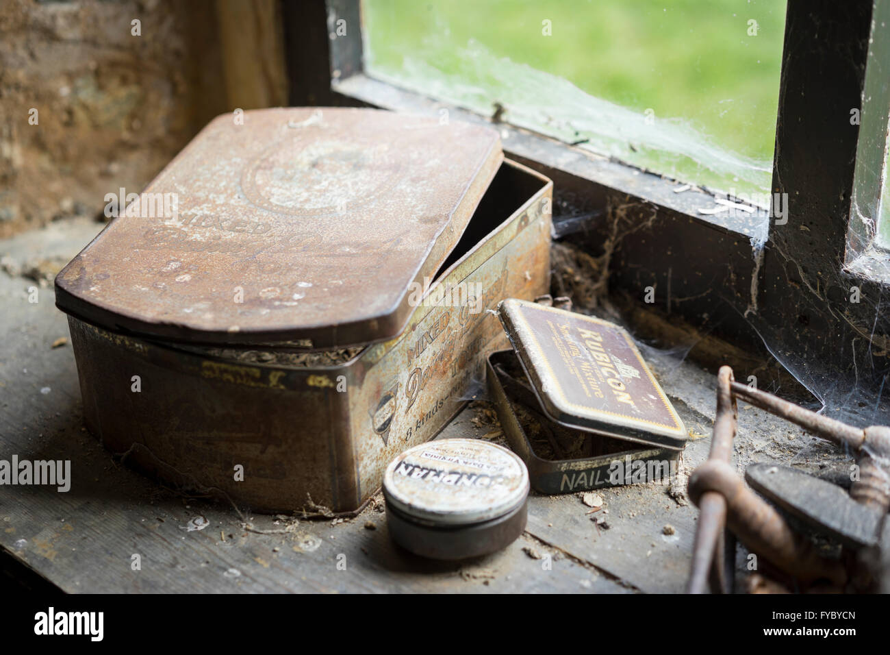 Old tins on a windowsill inside the stables in the village of Tyneham, Dorset, which was abandoned during the second - Stock Image