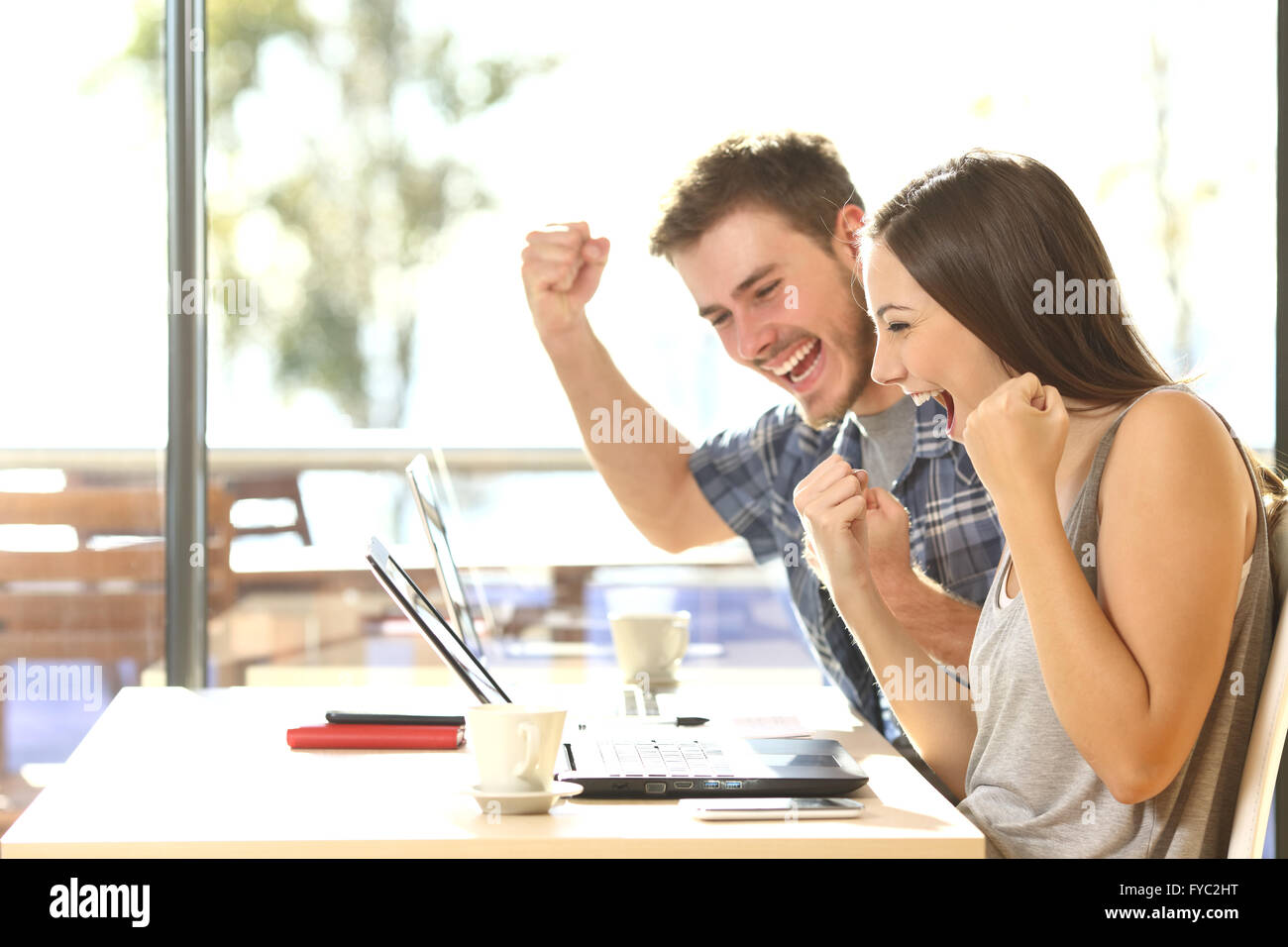 Group of two young euphoric students watching exam results in a laptop in a table of an university campus bar - Stock Image