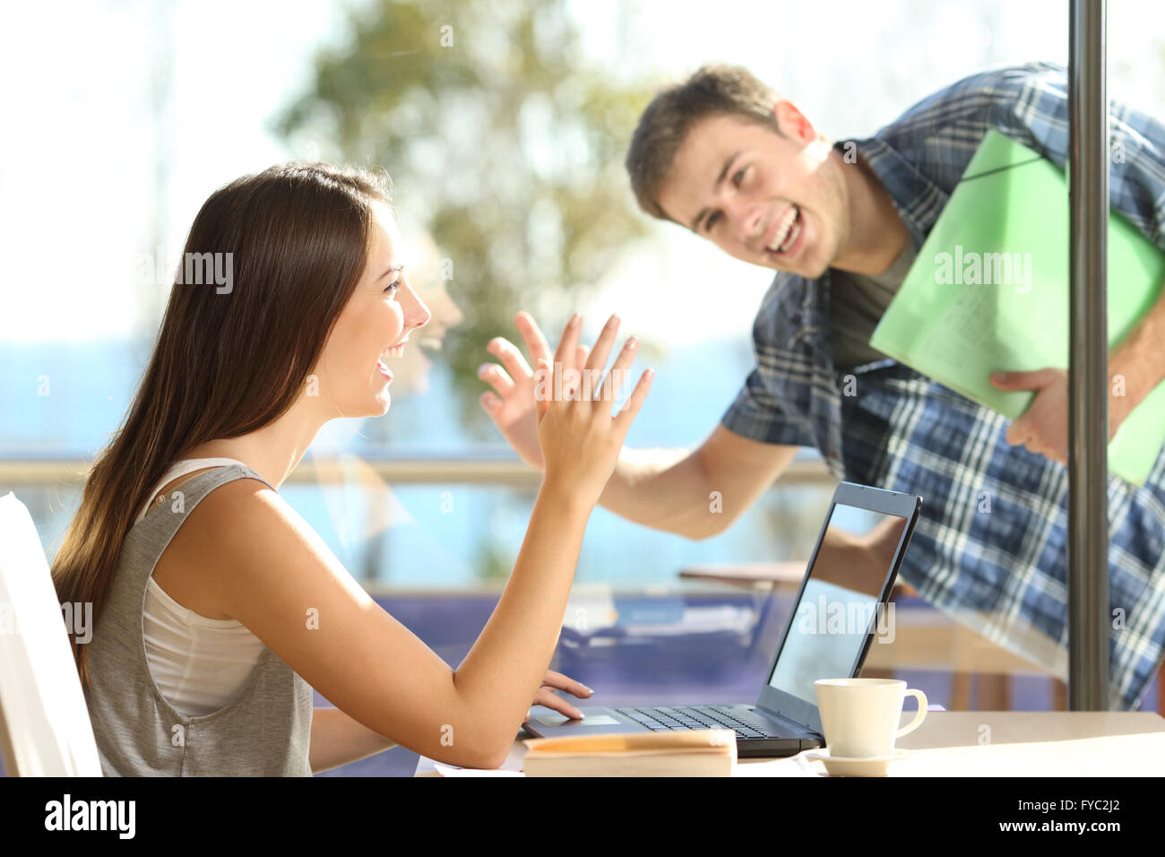 Happy friends or couple greeting waving hands and looking each other in a date in a coffee shop - Stock Image
