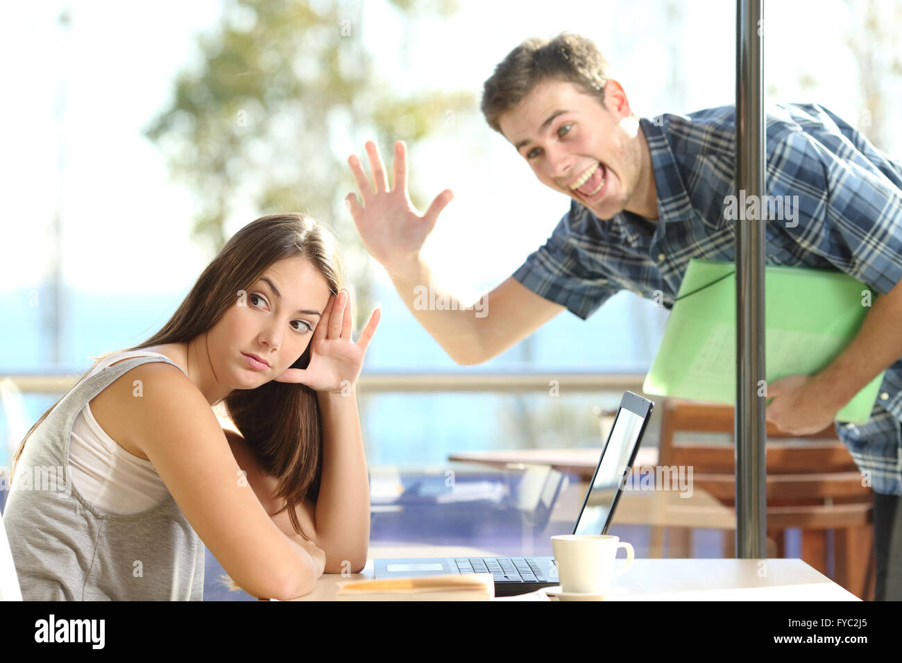 Girl ignoring and rejecting to a stalker man waving her in a coffee shop in a blind date - Stock Image