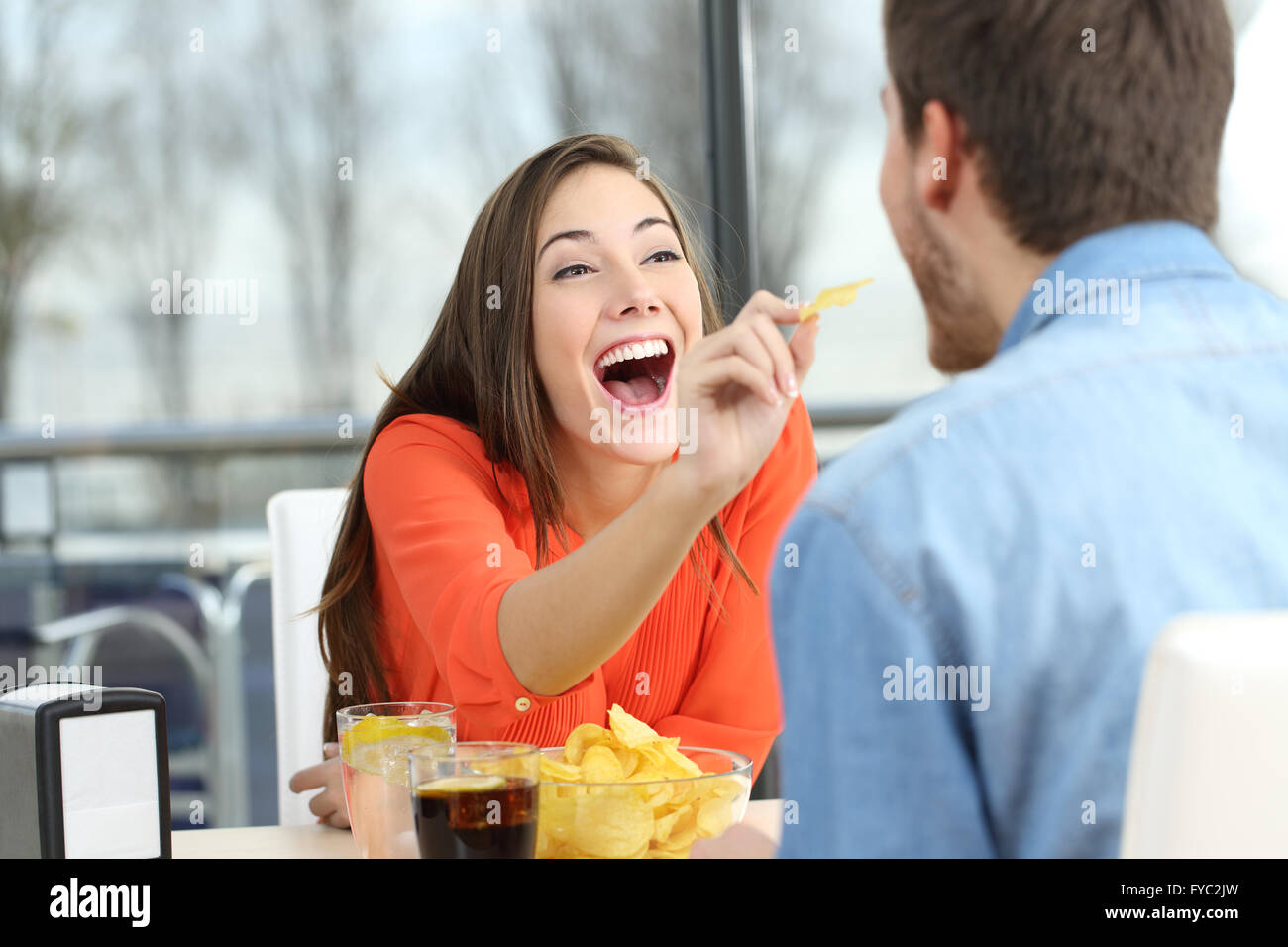 Playful couple eating chip potatoes and joking looking each other in a date in a coffee shop - Stock Image