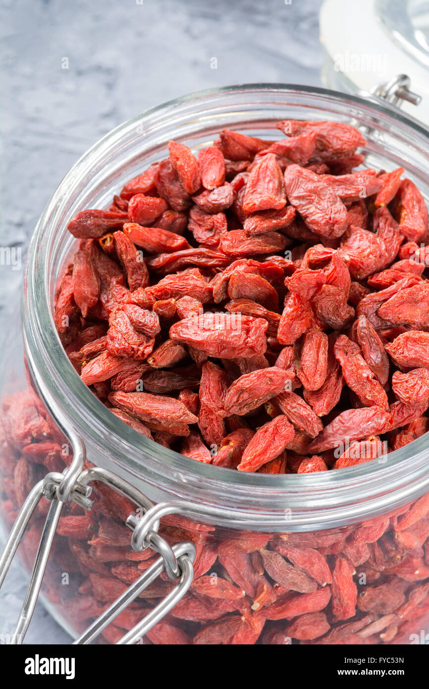Dried goji berries in a jar on textured background, selective focus. Superfood for healthy living, detox and power - Stock Image