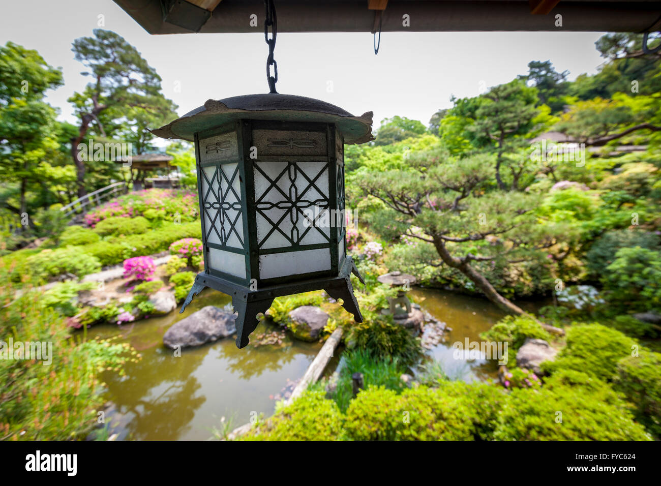 A Traditional Metal Lantern Hanging From A Veranda Which Overlooks A  Beautiful Japanese Garden   Stock