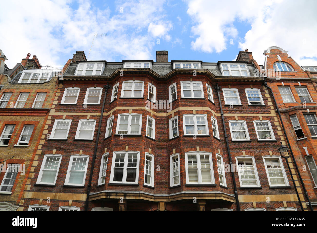 Traditional brick buildings in the Fitzrovia neighborhood in London. - Stock Image