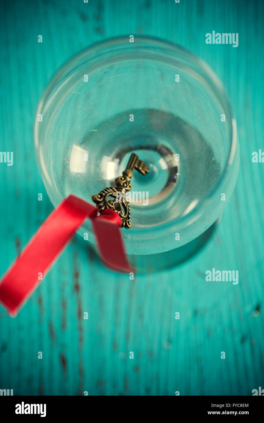 Old key with a red ribbon inside a glass - Stock Image
