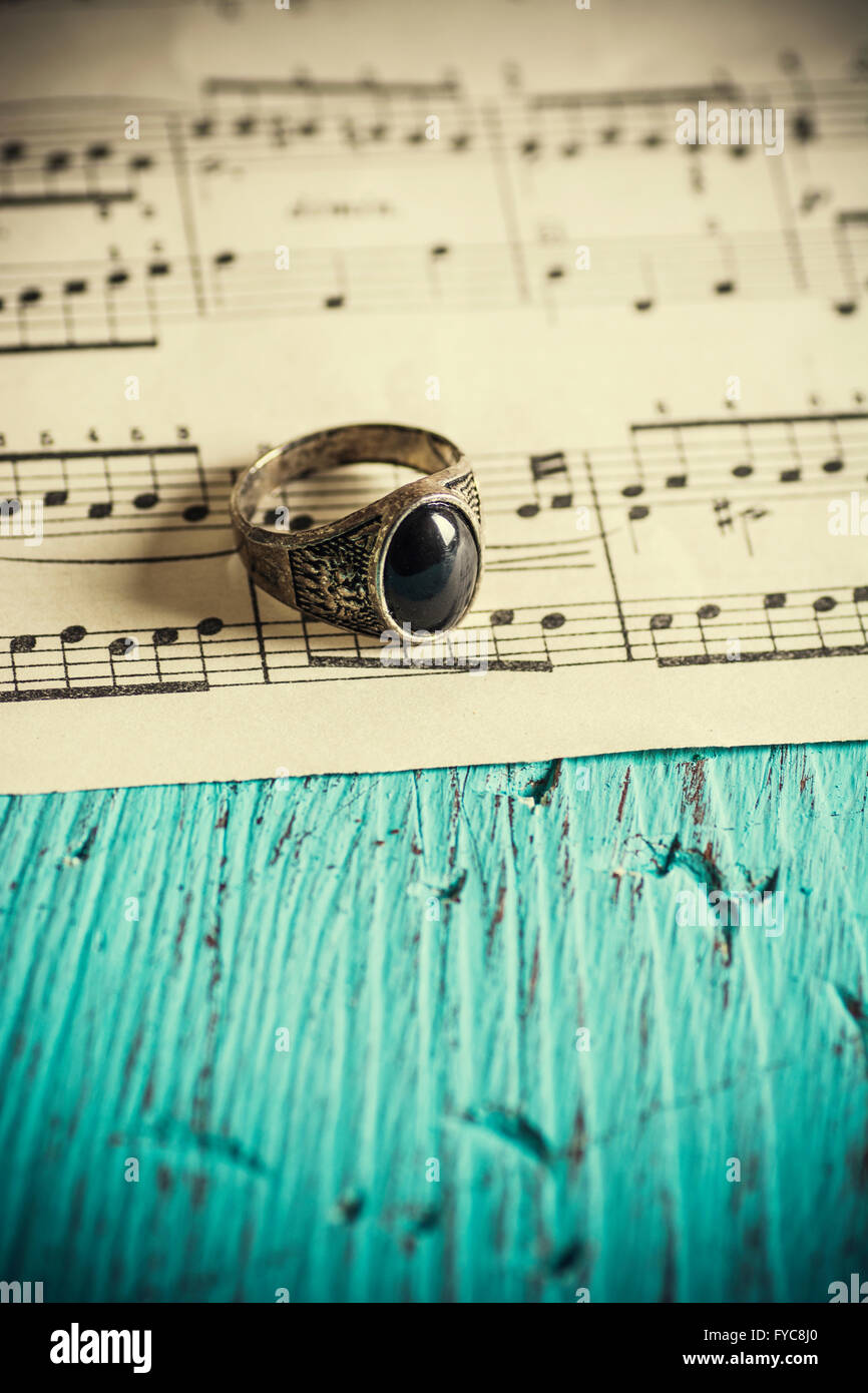 Vintage silver ring over a music sheet - Stock Image