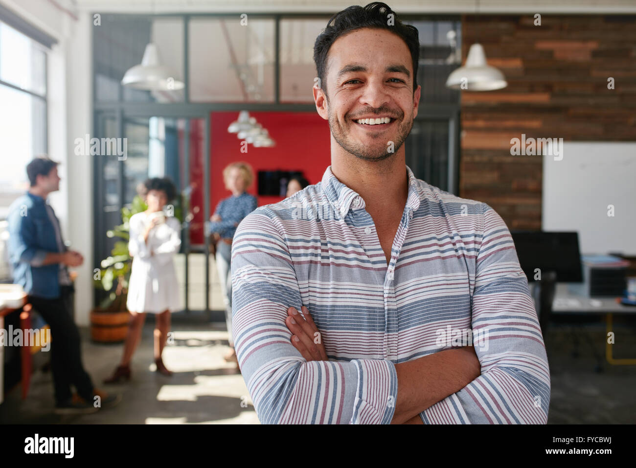 Portrait of a handsome young business man standing with arms crossed in an office. Smart caucasian young male designer - Stock Image