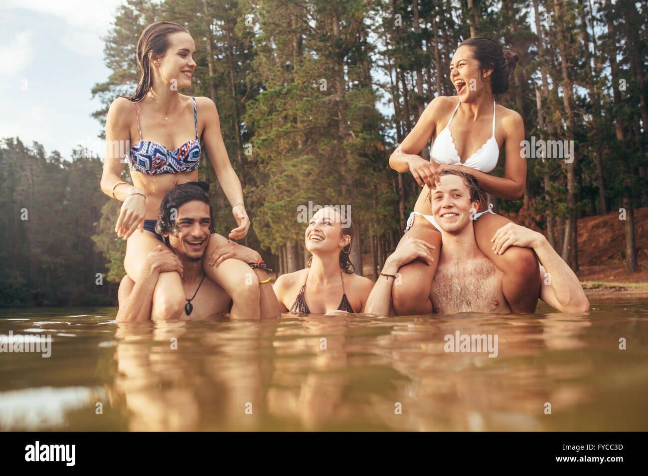 Portrait of young men in a lake carrying women on shoulders. Happy young friends enjoying a day at the lake. - Stock Image