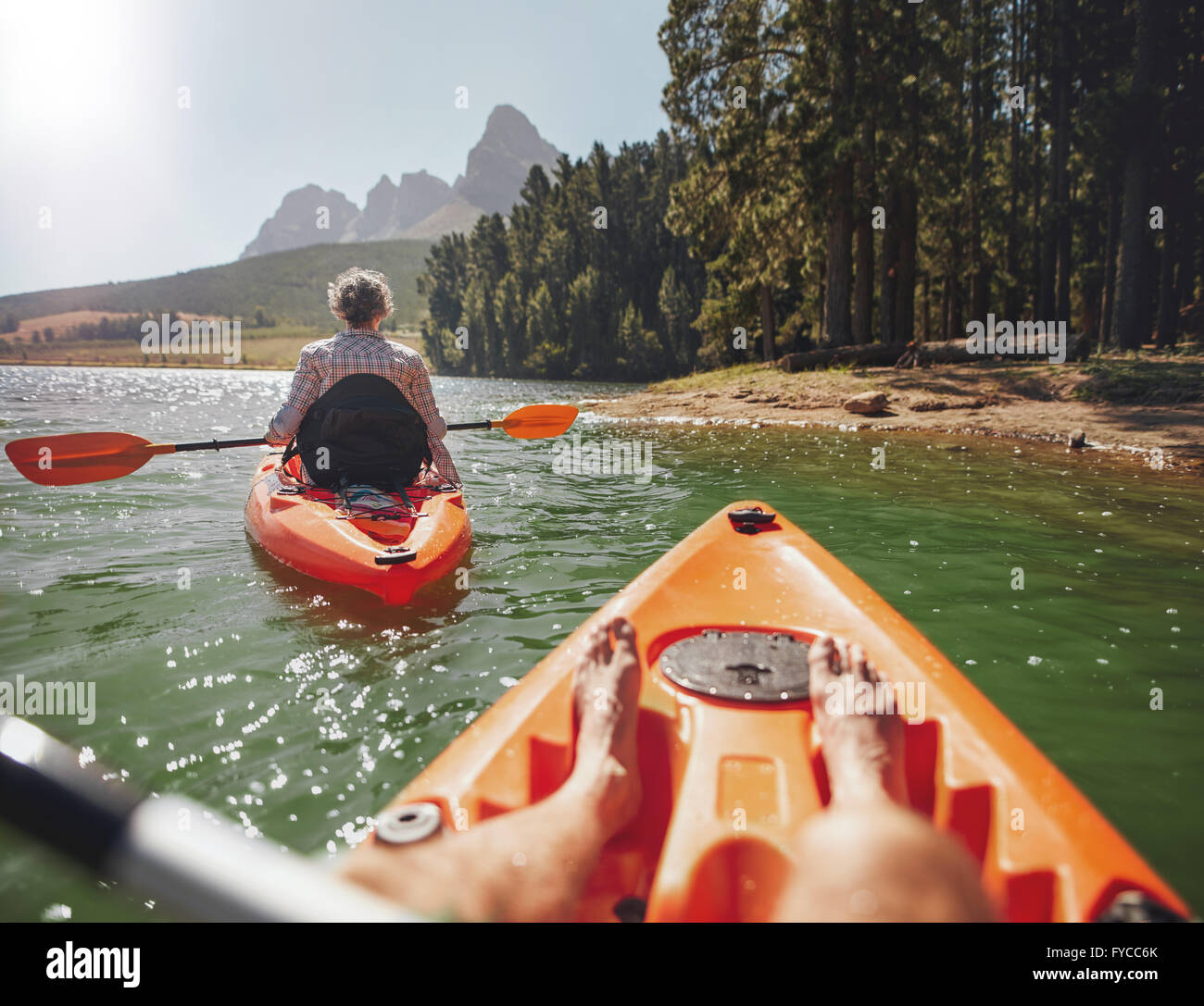 Couple canoeing in the lake on a summer day. Man and woman in two different kayaks in the lake on a sunny day. - Stock Image