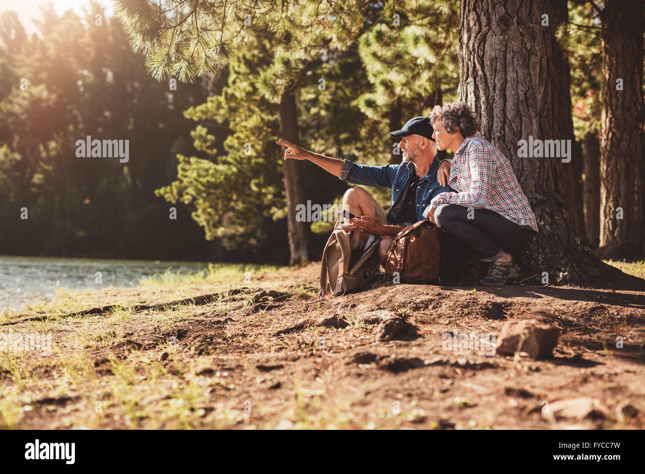 Mature couple sitting by a tree in forest with man showing something to woman. Senior man and woman on a hike in - Stock Image