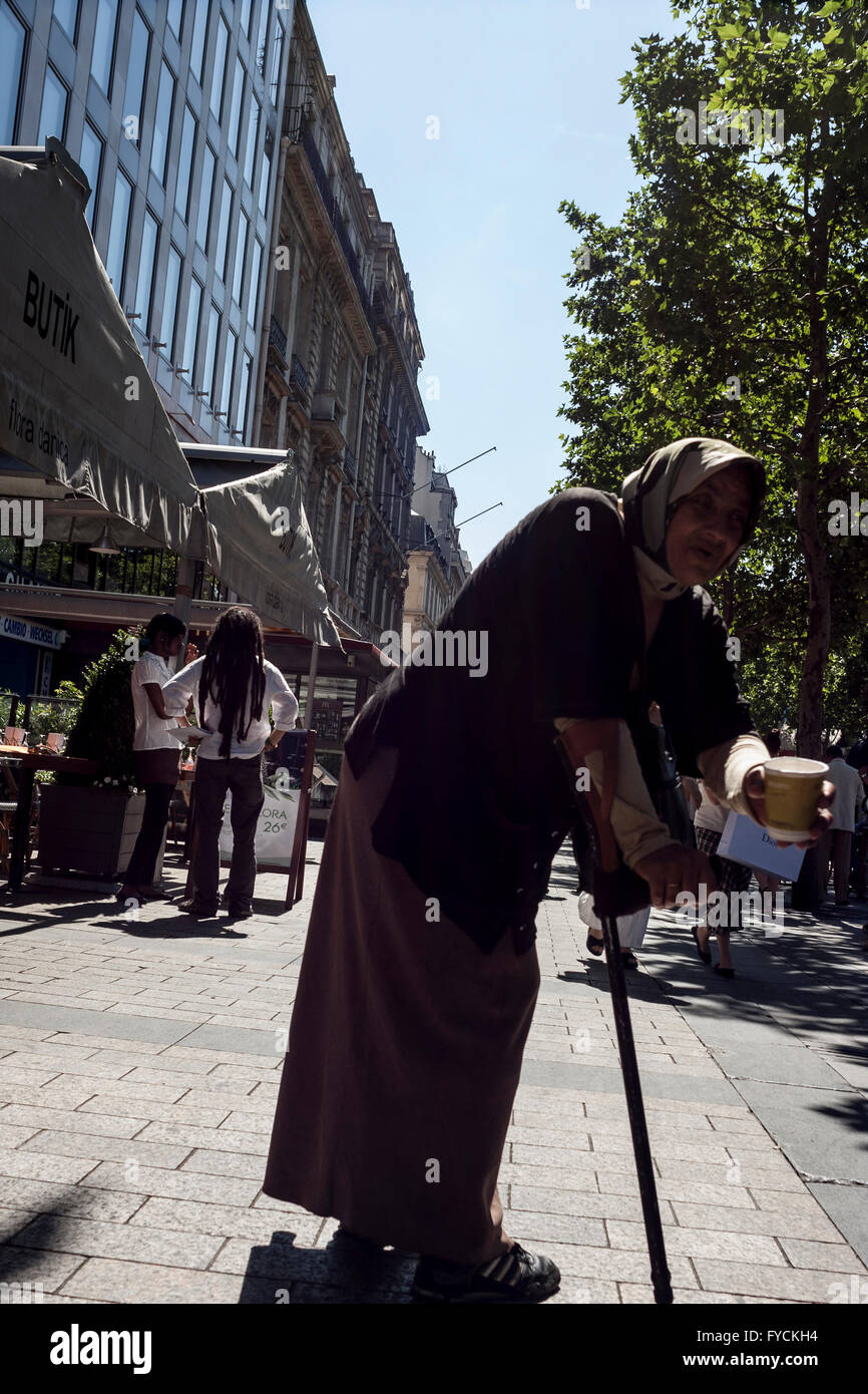 A Beggar asking for money in a busy street in Paris. France - Stock Image