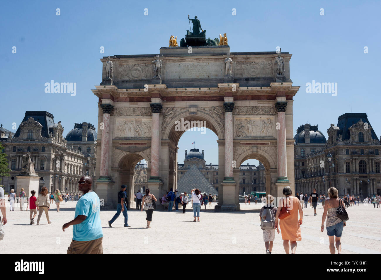 Members of the public walking next to remarkable building where is sited the Louvre Museum. Paris. France.  Pic - Stock Image