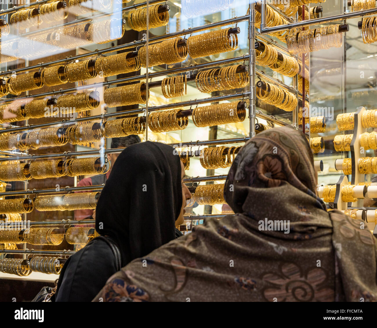 Two women in hijabs window shop in at jewelry shop in the Gold Souq, Al Ras, Dubai, UAE - Stock Image
