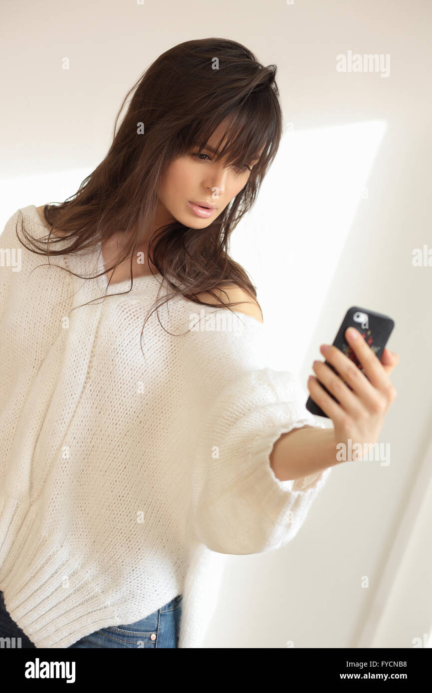 Young woman or teenage girl taking selfie with smartphone. - Stock Image