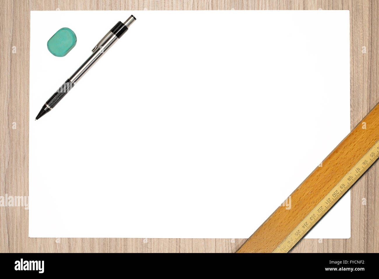 Blank paper with pencil, ruler and rubber on wood desk - Stock Image