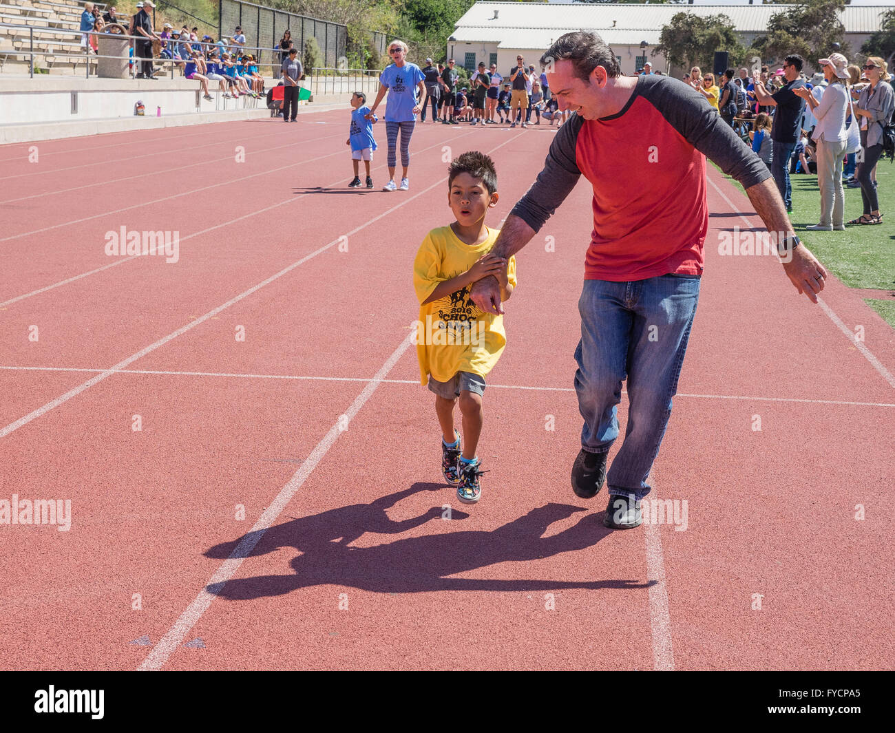 A father holds his disabled son's hand in a race at the Southern California Special Olympics held at in Santa - Stock Image