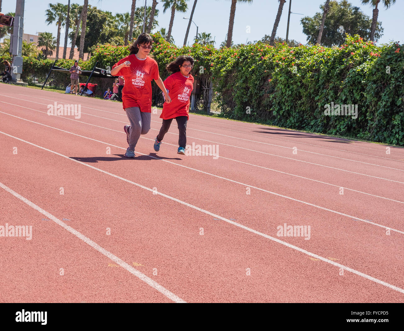 An adult helper helps a disabled girl race in a 50 meter race at the Southern California Special Olympics held in - Stock Image