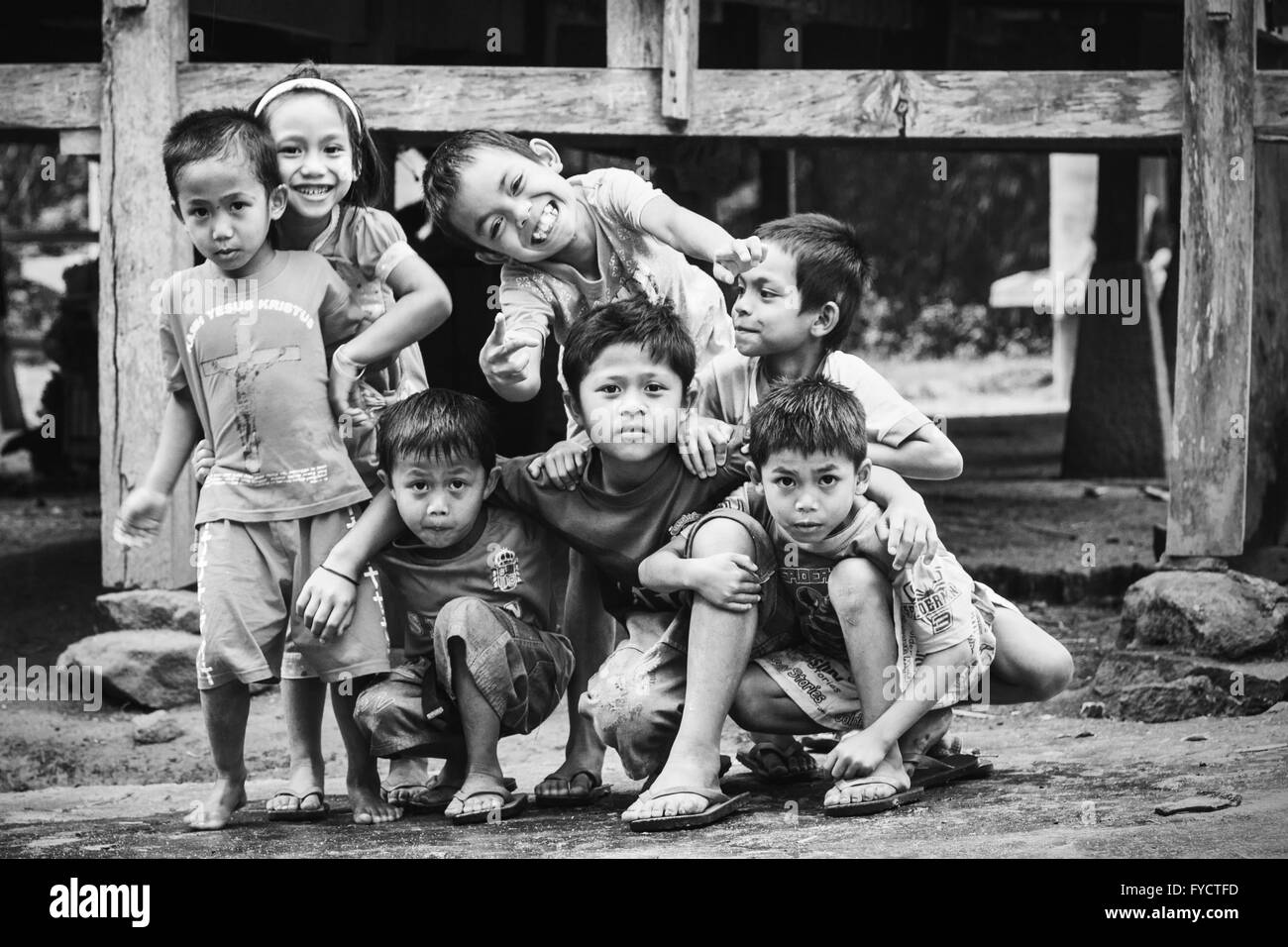 Group of cheerful children laugh and smile for a candid photograph outside a Tongkonan house in Sulawesi, Indonesia - Stock Image