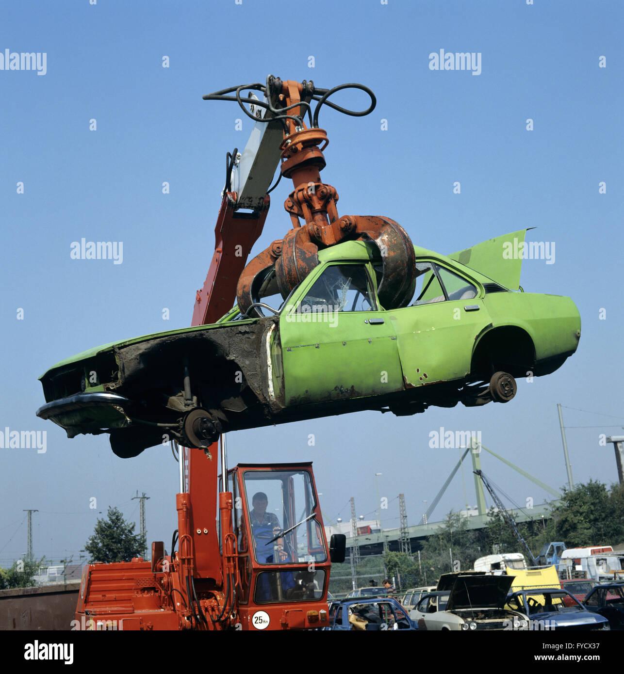 Scrap car hangs on the excavator grab Stock Photo