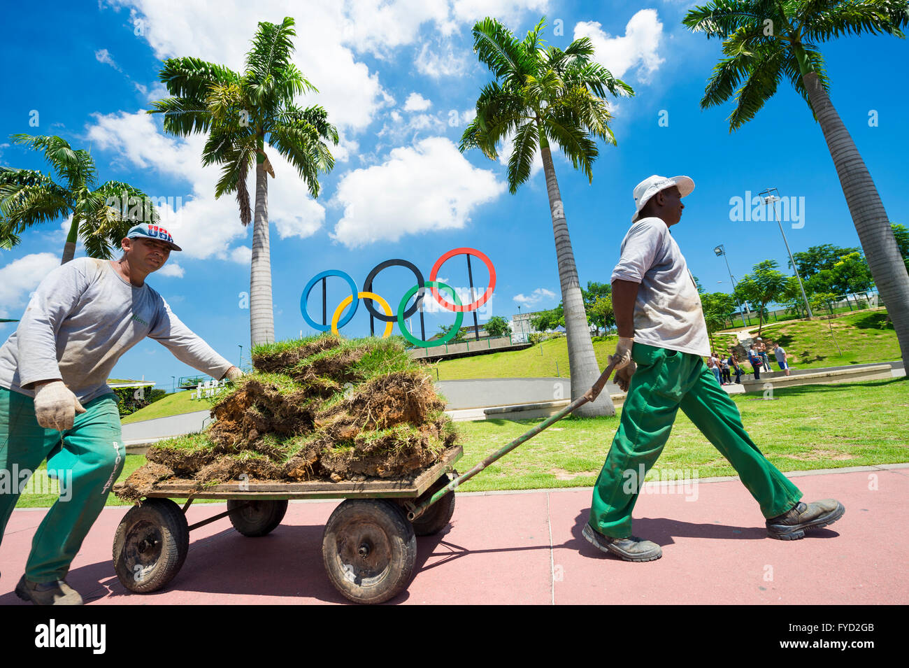 RIO DE JANEIRO - MARCH 18, 2016: Maintenance workers transport landscaping materials in front of Olympic Rings. - Stock Image