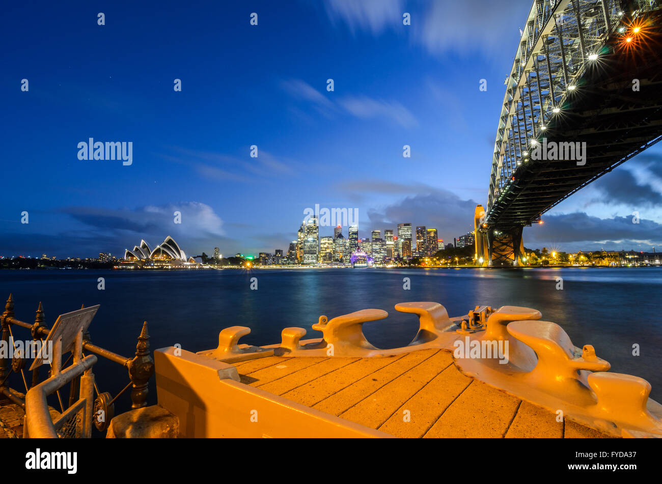 Sydney Harbour, the Sydney Opera House and Circular Quay as seen from Milson's Point and the bow of HMAS Sydney. - Stock Image