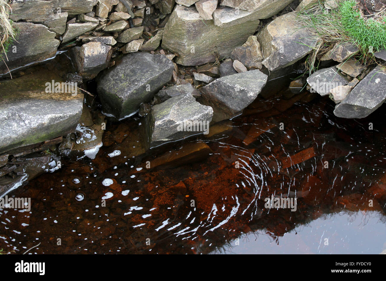A bank of stones on the edge of a small pool of peat-coloured water on a freshwater stream on the island of Arranmore, Stock Photo